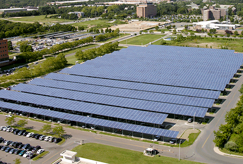 Solar panels are installed over parking spaces to maximize solar energy collection.