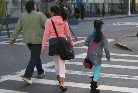 Children walking in a crosswalk on their way to school in New York City.