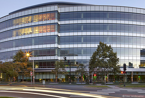 The curved glass wall office building at 300 Binney Street in Cambridge, Massachusetts is pictured at dusk.