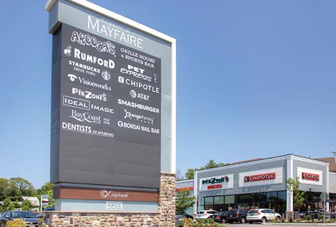 Entryway sign showing a list of businesses at the Shoppes at Wayfair in Attleboro, Massachusetts.