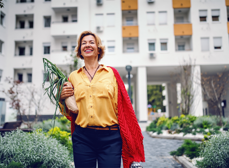 A woman carries greenery in a walkable community.