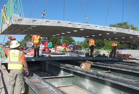 Construction personnel move part of the bridge deck into place during the Colchester Bridge replacements.