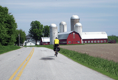 A bicyclist on a rural Vermont road near a red barn.