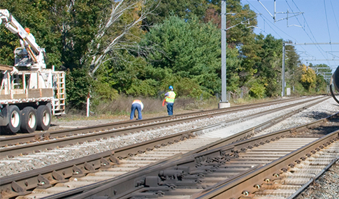 Two men work alongside railway tracks.