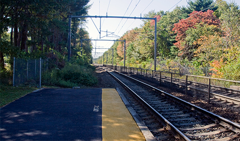 Autumn trees surround both sides of railway tracks coming into a station.