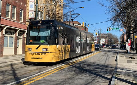 A modern streetcar runs through a street in Atlanta lined with historic buildings
