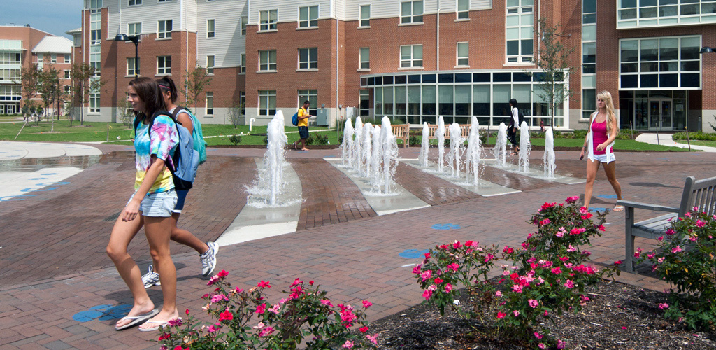 Students pass a water feature as they walk through Old Dominion University's Campus on a sunny day