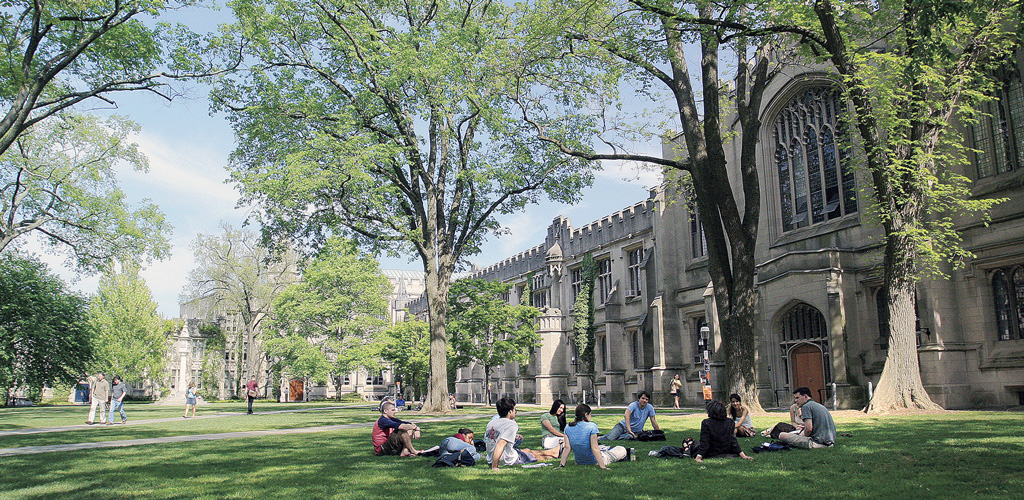 Students sit in the grassy shade on Princeton University's campus