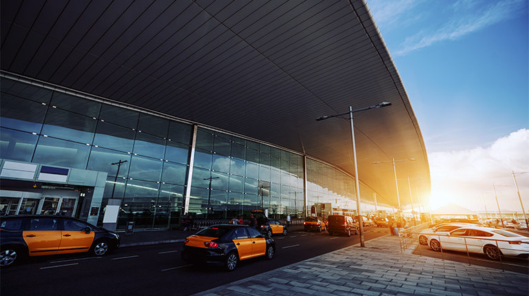 Cabstand in front of modern airport doors in Barcelona, cabrank with a lot of taxis near windowed facade of contemporary Airport terminal in Spain with road, long ceiling and parking