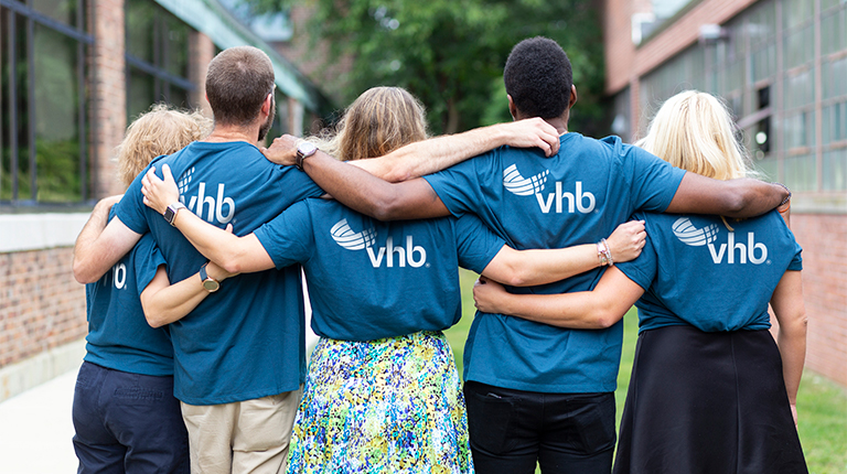 Five VHB employees standing side by side wearing blue VHB t-shirts