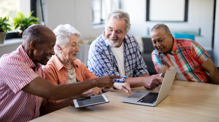 A group of elderly people are sitting at a table looking at a laptop computer and tablet together.