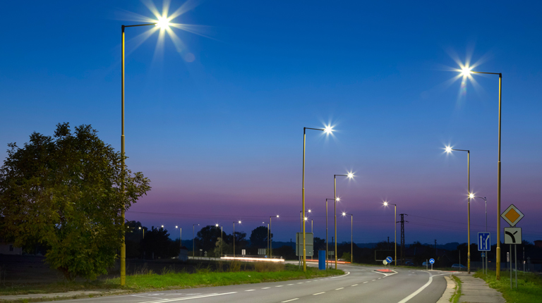Street lights light up the evening sky at a turn on suburban road lined by trees
