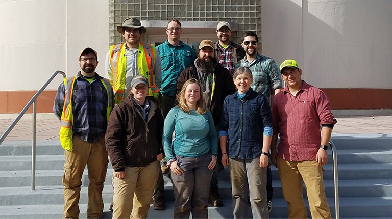 A team of archaeologists stand on the steps of a National Park Service building
