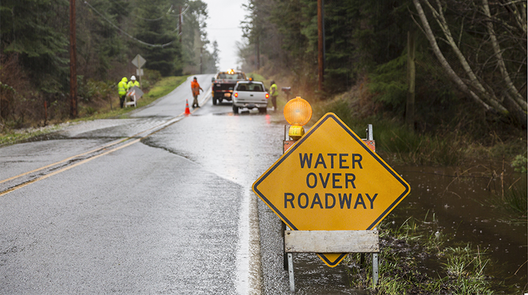 Emergency workers placing warning signs on flooded road