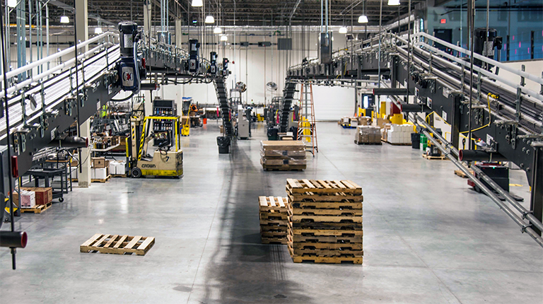 Pallets are stacked and automated machinery is shown centered inside a large industrial distribution warehouse