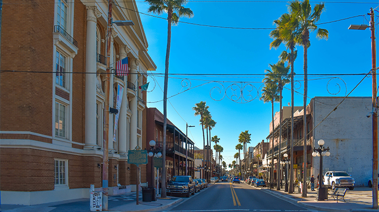 A street lined by historic buildings, cars, and tall palms